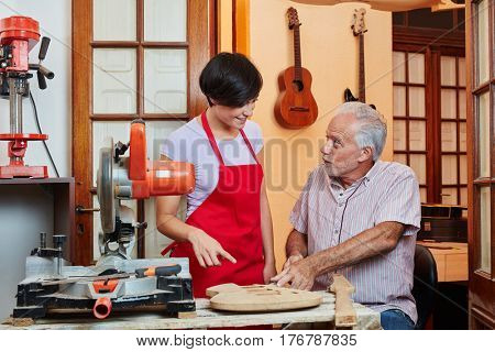 Young woman as trainee learns with master luthier in workshop