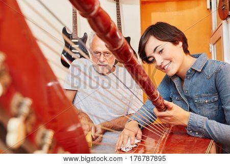 Young trainee cleans harp at luthier's workshop