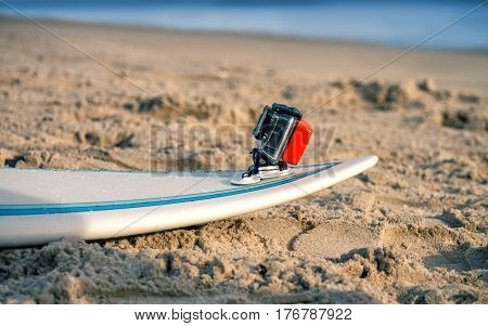 Surfboard with attached action camera lies on the sand on the beach. Action camera is in waterproof case for swimming.