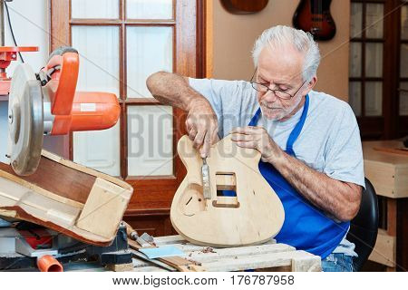Senior guitar maker makes new guitar with care at luthier's wood workshop