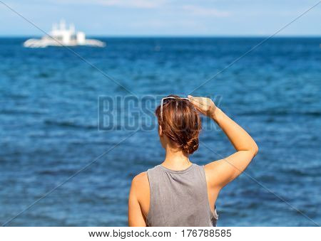 Woman looking at sea. Trendy casual photo of girl watching cruise boat. Seaside vacation travel banner template. Seashore blue water of tropical lagoon. Sunny weather background. Yong girl on beach