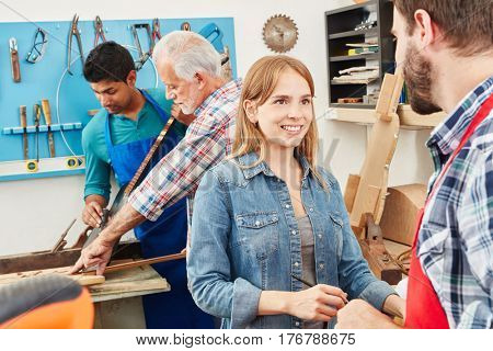 Young woman as trainee in carpenter's workshop