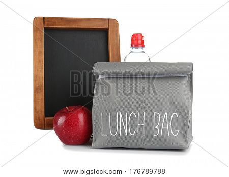 Modern lunch bag, blackboard and apple on white background