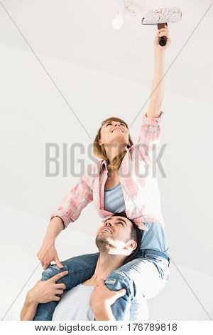 Woman on man's shoulders painting ceiling with paint roller
