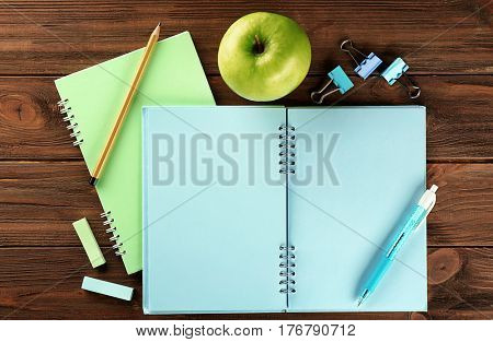 Open exercise book and appetizing green apple on wooden background