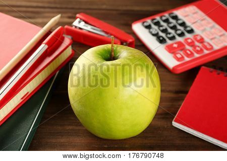 Appetizing green apple and stationery on wooden background