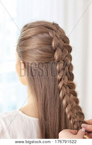 Young beautiful woman with nice braid hairstyle on light background