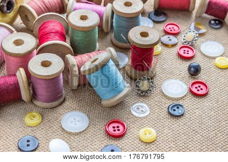 sewing tools (many different colorful thread needle many different buttons) on wooden background