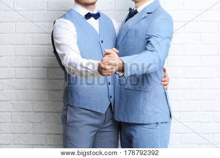 Happy gay couple dancing against brick wall background