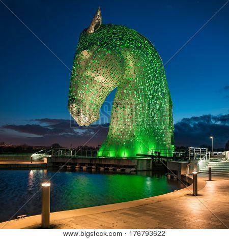 FALKIRK SCOTLAND - MARCH 16 2017: The head of a Kelpie horse sculpture at The Helix Park in Falkirk Scotland illuminated in green to commemorate St Patrick's Day. The Kelpie structures are the work of artist Andy Scott.