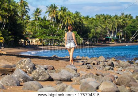 Lonely woman walking on tropical beach. Pretty girl walks on beach. Romantic seashore blue sea and coco palm trees. Summer vacation casual photo. Relaxed day by the sea. Solo holiday concept image
