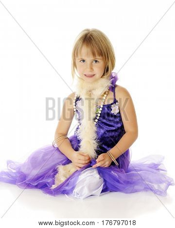 A pretty young elementary girl sitting in a beautiful purple dress with pearls and a pale pink boa.  On a white background.