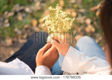 View over shoulder young man being giving bouquet white flower for girlfriend in public garden sunset time have small lake background