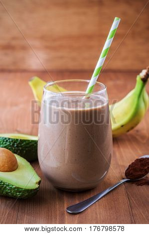 Healthy chocolate avocado banana smoothie on wooden background