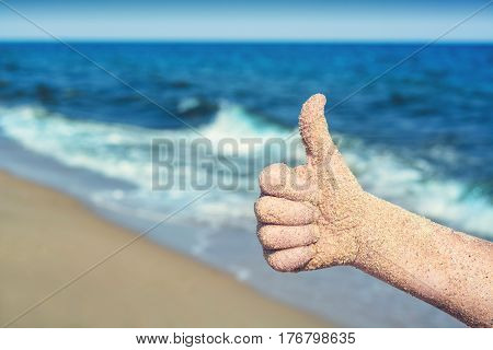 Close-up picture of child's hand on the beach against blue sea with waves. Hand showing thumbs up or shows good and like.