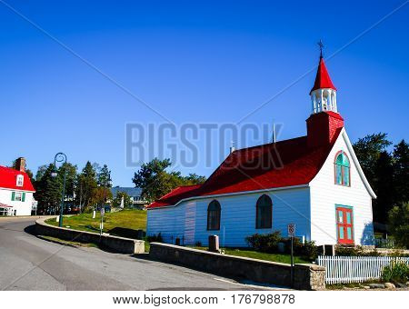 small red and white church in tadoussac canada on a blue sky background