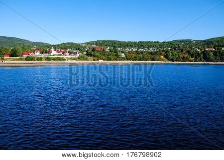 view of tadoussac bay in canada from a ferry boat on blue sky and water backgrounds