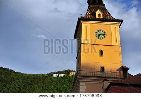 Brasov townhall with a sign on the hill on background