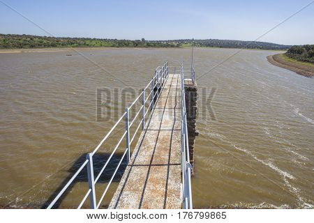 Modern footbridge attached to Roman Dam of Cornalvo Reservoir. This monument is still in use nowadays Extremadura Spain