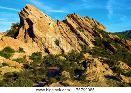 Rocks uplifted from the San Andreas Fault surrounded by chaparral shrubs taken at Vasquez Rocks in the Mojave Desert, CA
