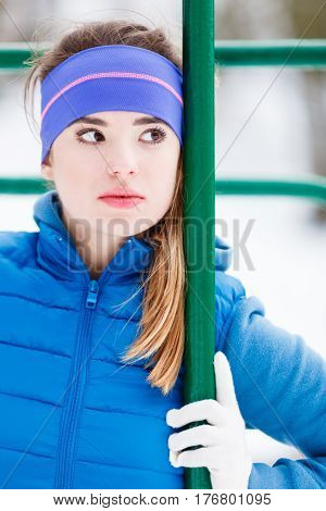 Outdoor sport exercises sporty outfit ideas. Woman wearing warm sportswear relaxing after exercising outside during winter.