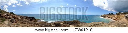 Panoramic of Cupecoy in St. Martin/St. Maarten showing the interesting geological rock formations with Caribbean sea and interesting sky.