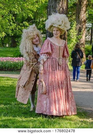 Saint Petersburg, Russia - may 15, 2016: Actors demonstrate vintage clothing 18 century in the Park. Man and woman in historic clothes of the 18th century lead the conversation on the background of green meadows and wood