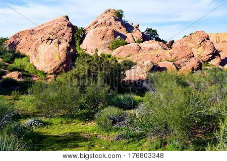 Rural rocks surrounded by lush green desert chaparral grasslands taken at Vasquez Rocks in the Mojave Desert, CA