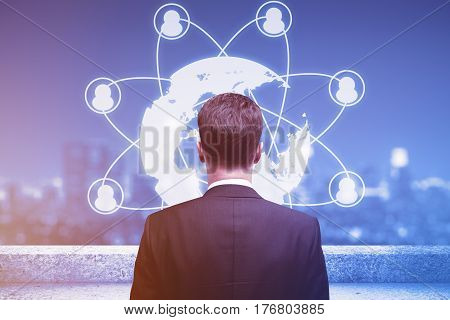Back view of young businessman on rooftop looking at abstract globe with connected people icons. Night city view in the background. HR concept