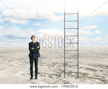 Young businessman with folded arms standing in desert and looking up at ladder leading to the sky. Success and growth concept