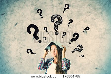 Pretty caucasian girl with question marks on concrete wall background. FAQ concept