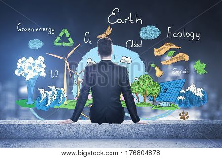 Back view of businessman sitting on rooftop with creative eco sketch. Blurry night city view background. Go green concept