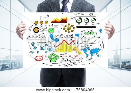 Businessman in suit holding whiteboard with business sketch in interior with panoramic city view. Success concept