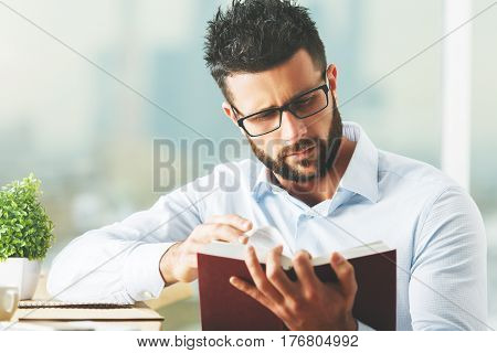 Close up portrait of attractive european man reading book at modern workplace with decorative plant and other items. Knowledge concept