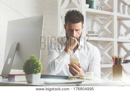 Worried young man at modern workplace using cellphone