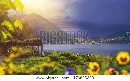 Beautiful waterscape of coastline of italian Varenna city with mountains on background leaf on foreground and dramatic sky before the rain