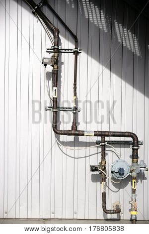 A gas pipe of copper with various valves and control modules on the outside of a building.