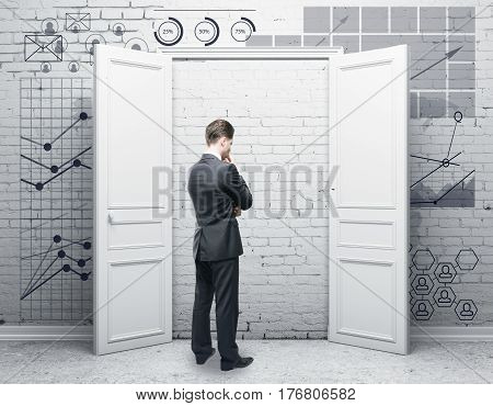 Thoughtful young businessman in abstract brick interior with door and digital business charts on wall. Finance concept. 3D Rendering