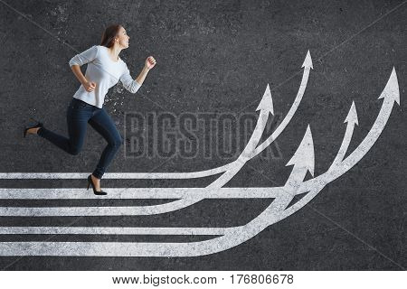 Side view of young caucasian woman running on drawn upward arrows on dark concrete background. Success concept