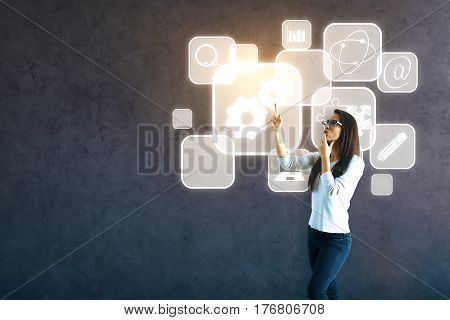 Attractive young woman pointing at concrete wall with teamwork research education and other business icons in cells