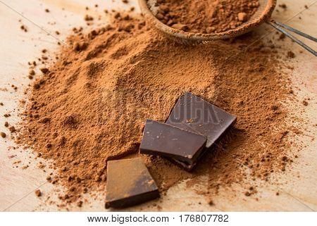 crude dark cocoa powder. Cocoa in a metal sieve on a blackboard