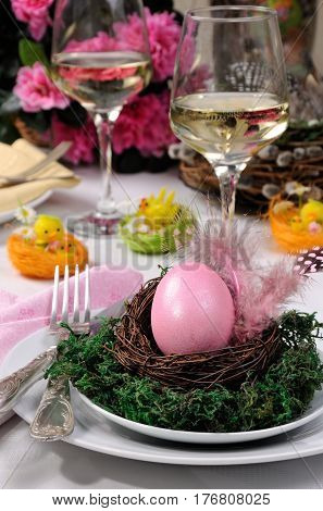 Decorative serving of the table for Easter. A painted egg in a nest on a plate with moss