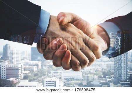 Businessmen shaking hands on modern city background. Coworking concept. Closeup Double exposure