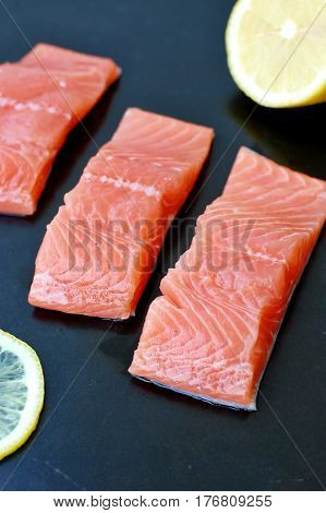 Raw Salmon Fillet With Yellow Lemon On Black Background