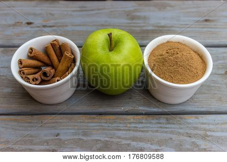 Green apple between two white porcelain bowls with cinnamon sticks and cinnamon powder.