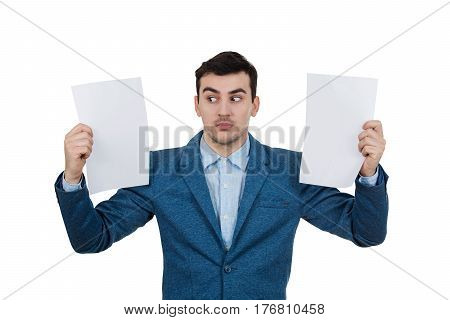 Scared young businessman holding two white papers and looking to right.Frightened facial emotion.