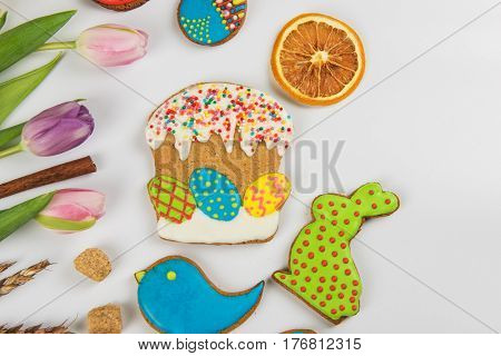 Tulips and gingerbread cookies on white background for Easter.