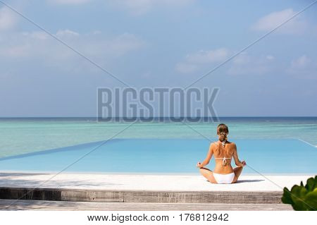 Meditation. Photo of a woman who is sitting in the lotus position on the ocean coast. Maldives.