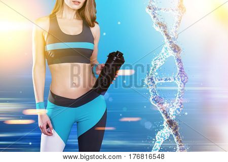 Close up of a sportswoman wearing a blue black and white sportswear and standing against blue background with a dna to her right. Toned image.