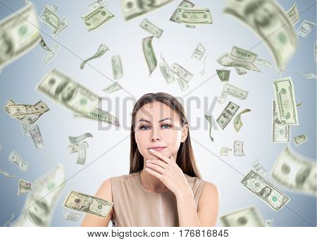 Portrait of a pensive woman in beige standing near a gray wall under a dollar rain. Concept of good money investment.